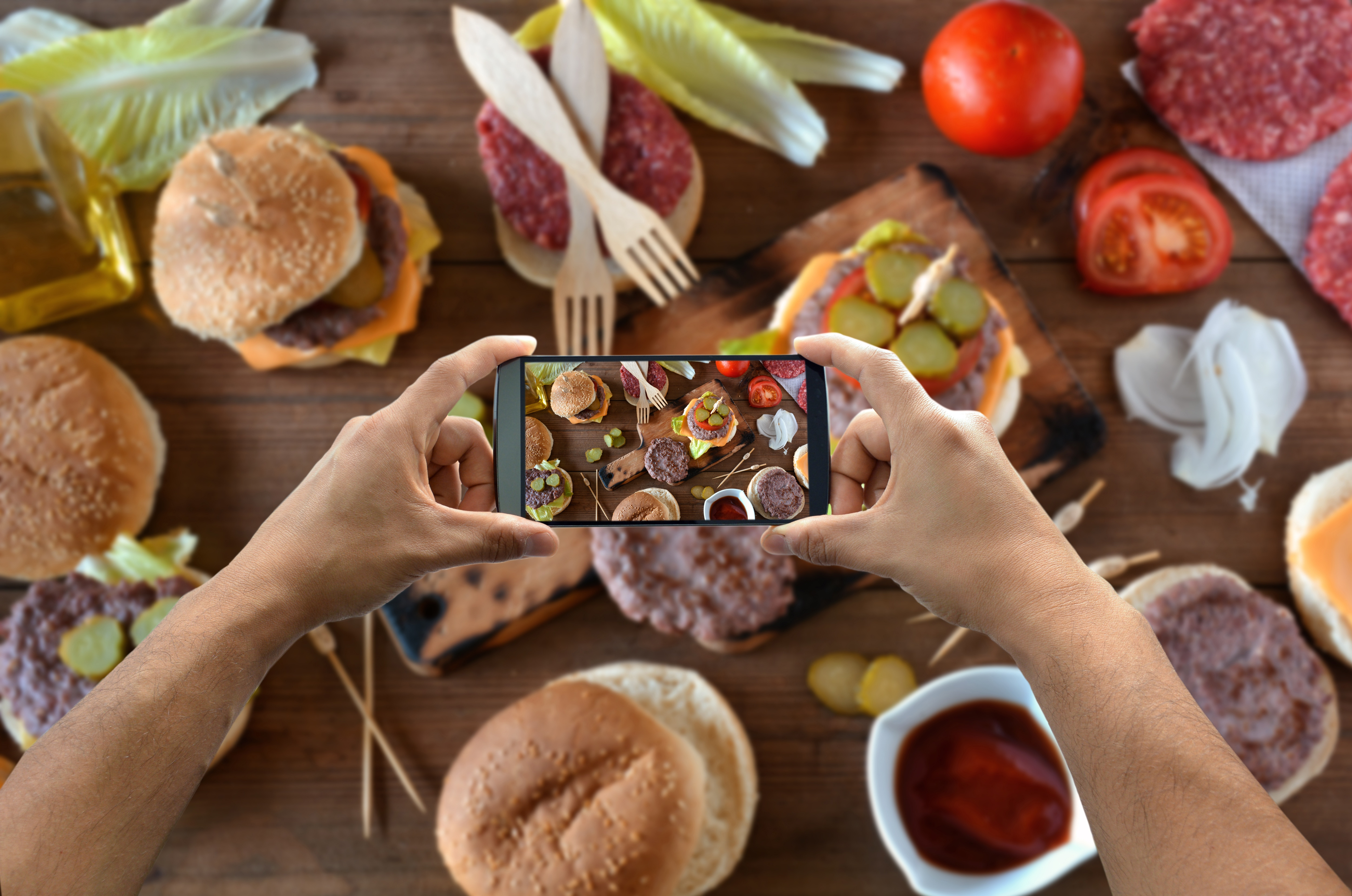 Instagram Publishing - A cellphone camera taking a picture of a burger table